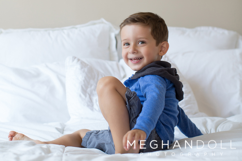 silly-little-three-year-old-boy-plays-on-big-white-bed
