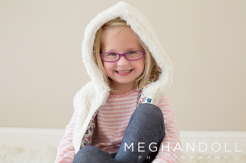 cute-five-year-old-twin-with-glasses-smiles-in-furry-vest