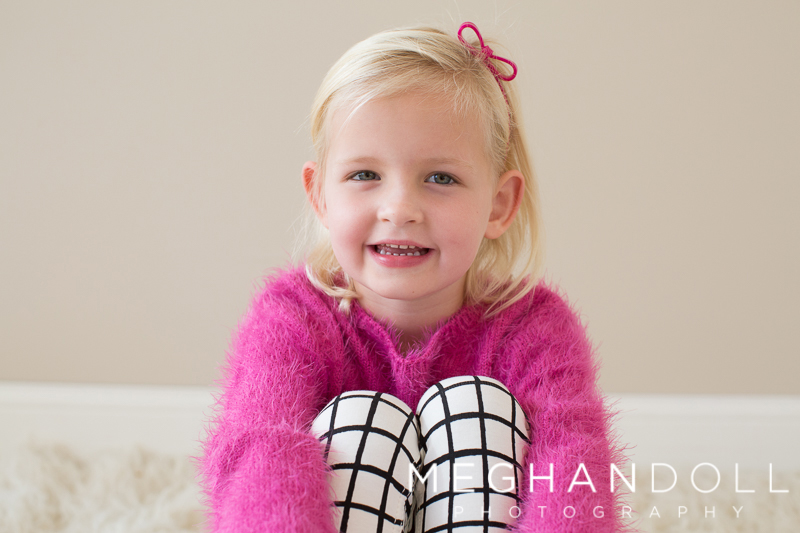 sweet-five-year-old-twin-smiles-in-fuzzy-pink-sweater