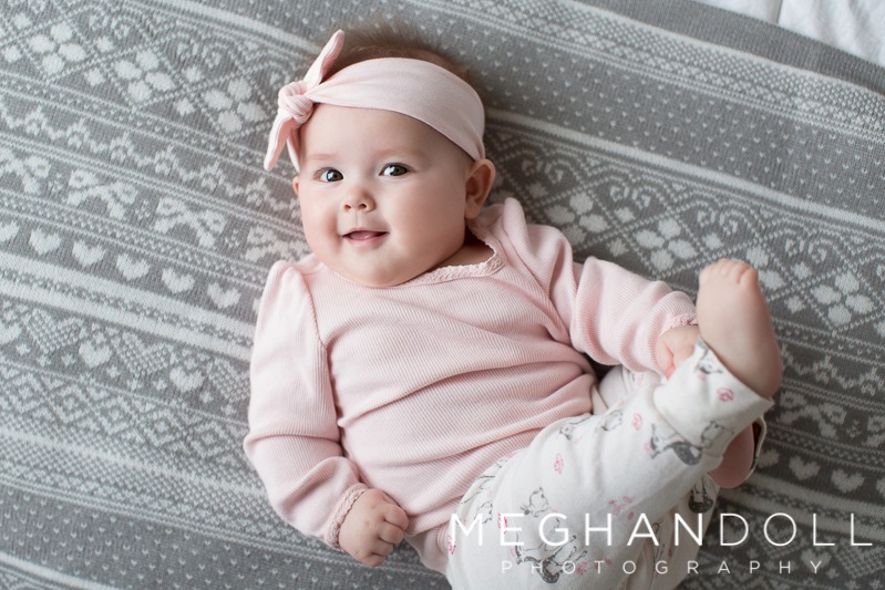 silly-six-month-old-baby-girl-plays-on-gray-blanket