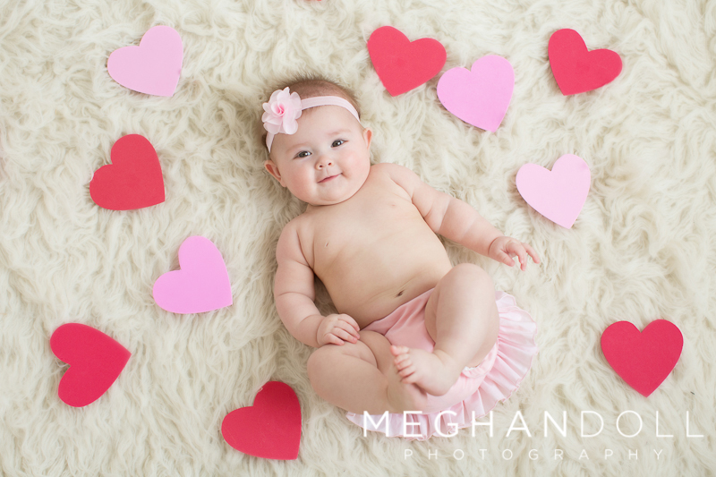 sweet-little-baby-girl-in-bloomers-lays-on-rug-surrounded-by-hearts