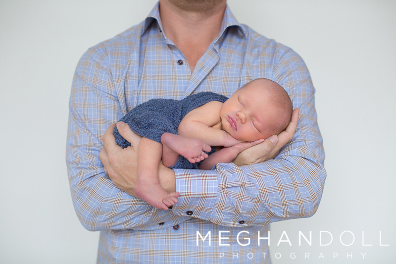 dad-in-blue-holds-his-newborn-little-baby-boy