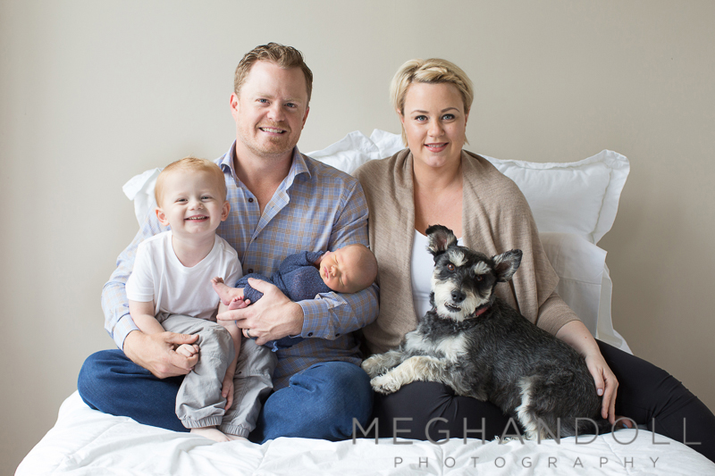 sweet-family-with-dog-shows-off-newborn-boy-on-big-bed