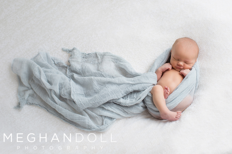 sweet-newborn-boy-wrapped-in-light-blue-on-big-white-blanket