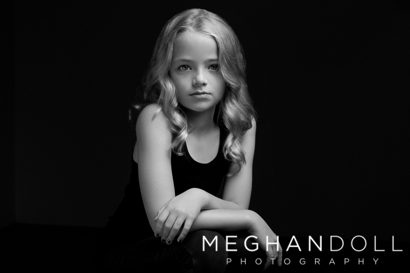 sweet-eight-year-old-girl-poses-with-serious-face-in-bw