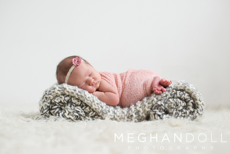 beautiful-newborn-girl-sleeps-on-curled-up-blanket