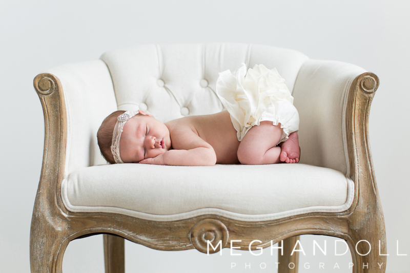 little-newborn-girl-sleeps-with-ruffles-on-big-chair
