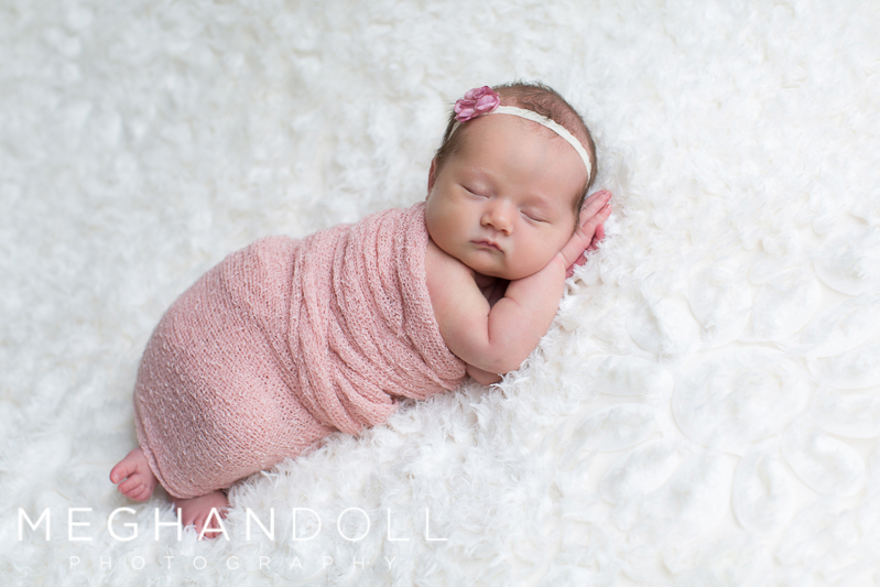 precious-newborn-girl-sleeps-on-flower-blanket