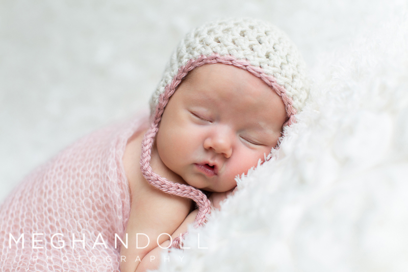 sweet-newborn-baby-girl-in-pink-and-white-hat
