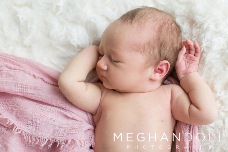 sweet-newborn-girl-stretches-her-arms-in-pink-wrap
