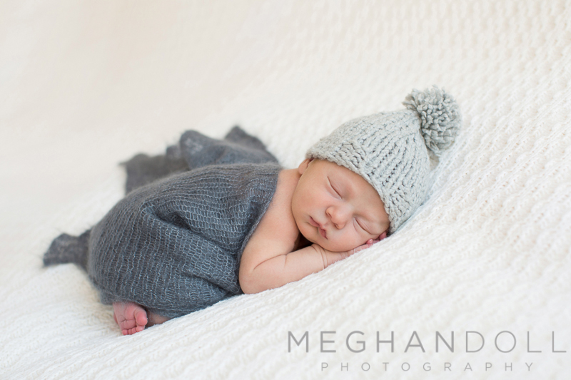 new-baby-boy-in-gray-sleeps-in-a-pom-pom-hat