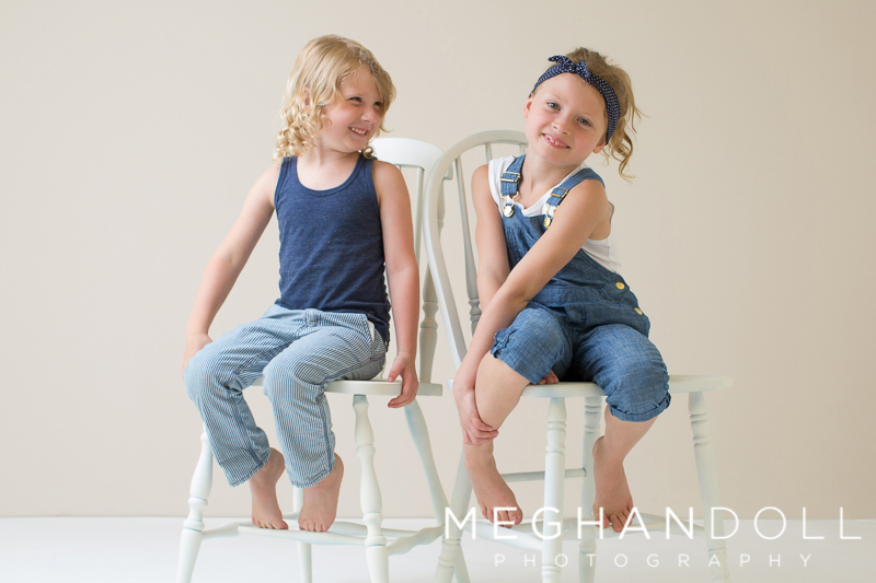 sweet-little-cousins-laugh-on-white-chairs