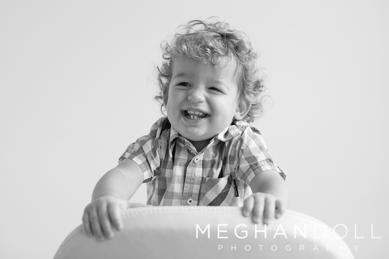 crazy-little-18-month-old-boy-laughs-on-big-white-chair