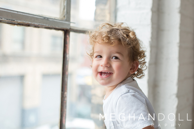 silly-18-month-old-boy-laughs-by-big-window
