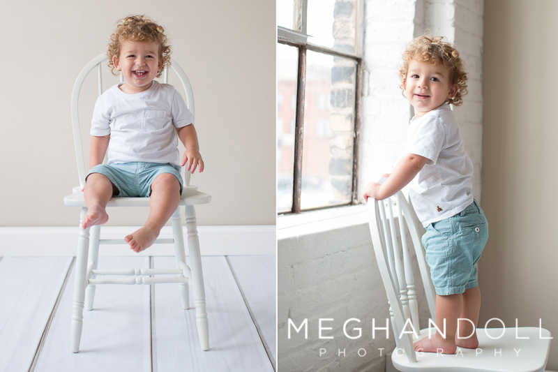 silly-18-month-old-boy-stands-on-big-chair-by-window