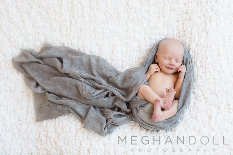 sweet-newborn-boy-smiles-on-big-blanket