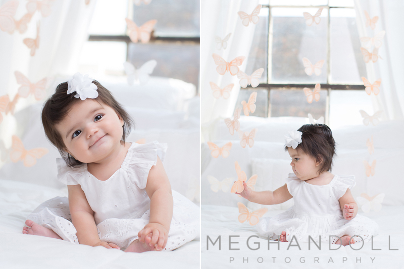 little-six-month-baby-girl-sits-on-big-white-bed-surrounded-by-butterflies