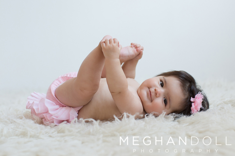 little-six-month-old-baby-plays-with-her-toes-on-big-rug