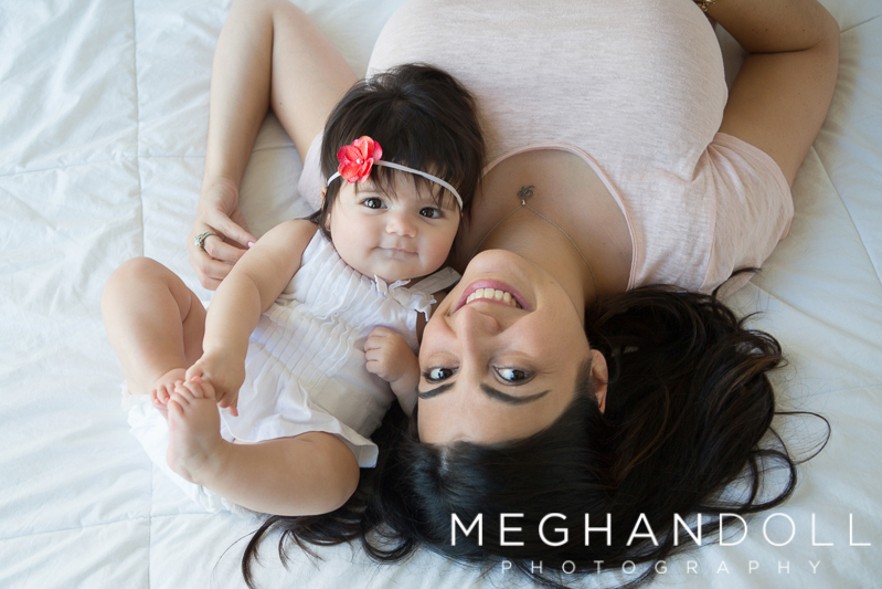 mom-and-sweet-six-month-old-baby-girl-lay-on-big-white-bed