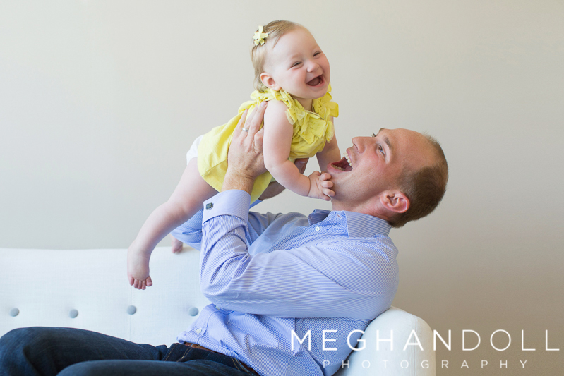 one-year-old-girl-in-yellow-dress-laughs-with-dad