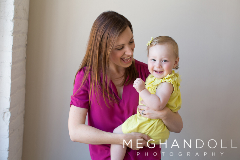 one-year-old-girl-in-yellow-dress-smiles-with-mom