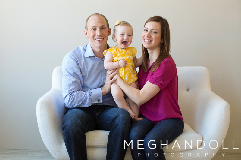silly-one-year-old-girl-in-yellow-laughs-with-parents