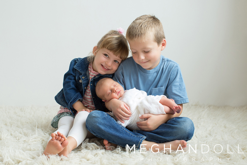big-brother-and-sister-hold-their-new-brother