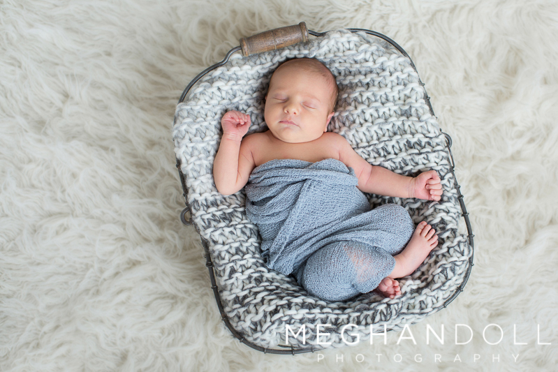 little-newborn-boy-sleeps-in-wire-basket