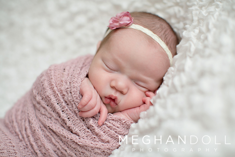 close-up-of-little-baby-in-pink-sleeping-on-white-blanket