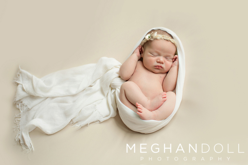 new-little-baby-girl-wrapped-in-white-sleeps-curled-up-on-tan-blanket