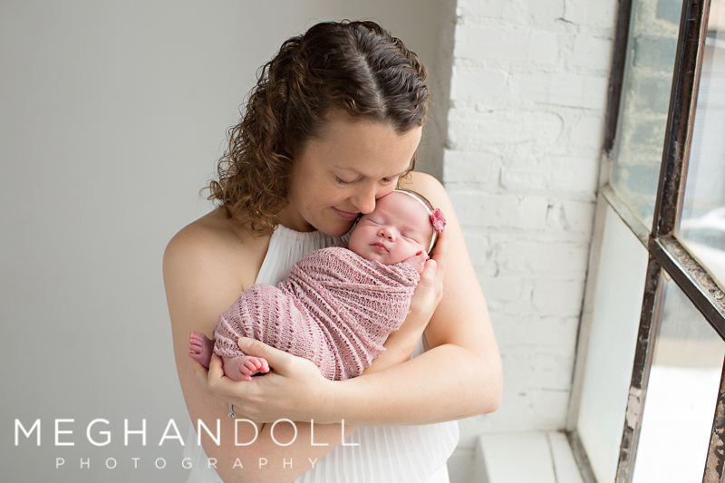 mom-in-white-dress-holds-her-new-baby-girl