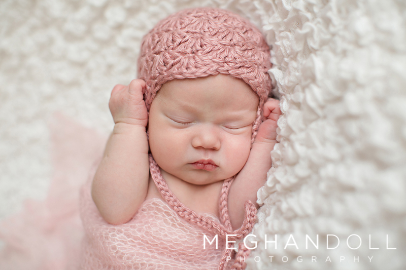 newborn-baby-girl-in-light-pink-hat-has-hands-up-by-her-face-while-sleeping-on-white-blanket