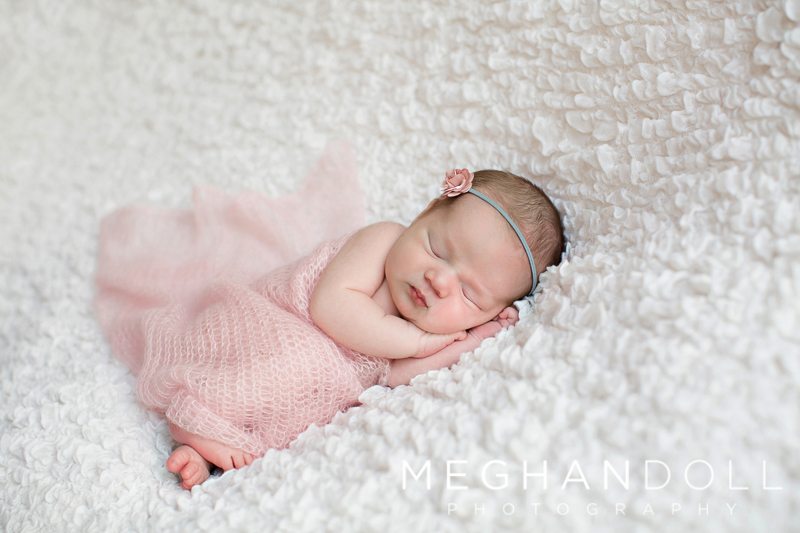 newborn-baby-girl-in-pink-sleeps-on-white-blanket
