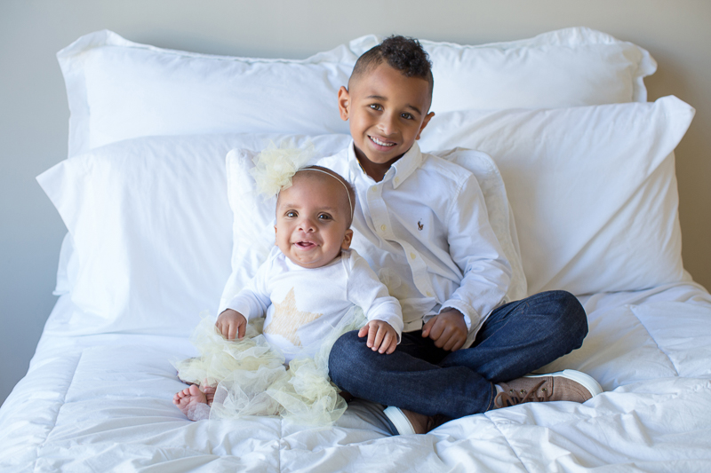 big-five-year-old-brother-holds-his-one-year-old-sister-on-big-white-bed