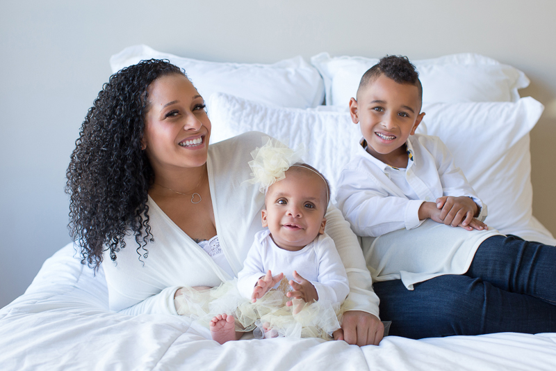mom-sits-on-big-white-bed-with-her-five-year-old-son-and-one-year-old-daughter