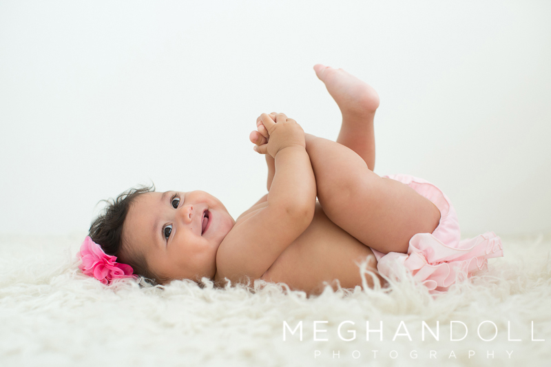 cute-six-month-girl-plays-with-her-toes