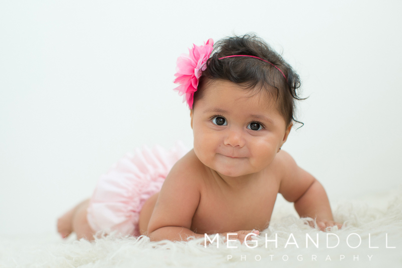sweet-six-month-baby-girl-in-pink-on-furry-rug
