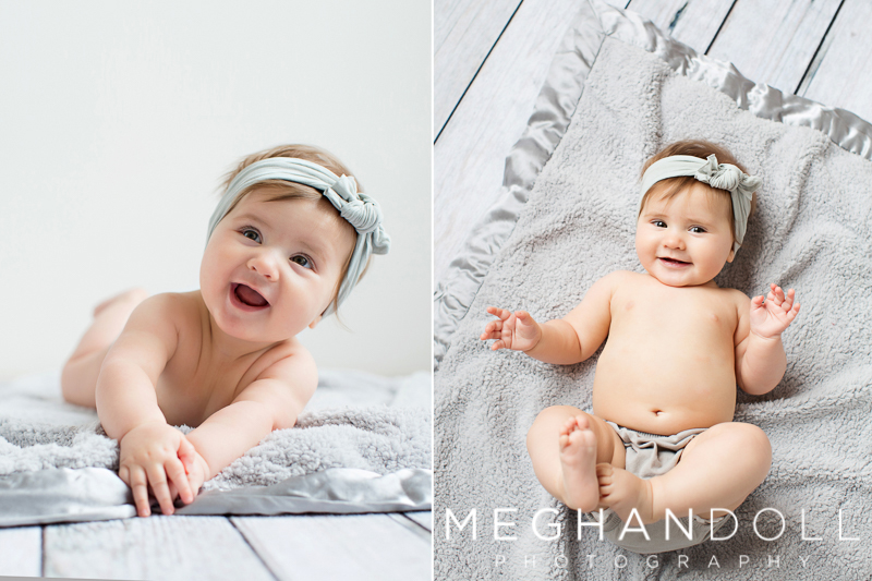 six-month-old-in-gray-headband-smiles-on-blanket