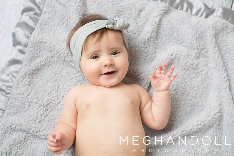 sweet-six-month-old-baby-in-gray-rolls-on-blanket