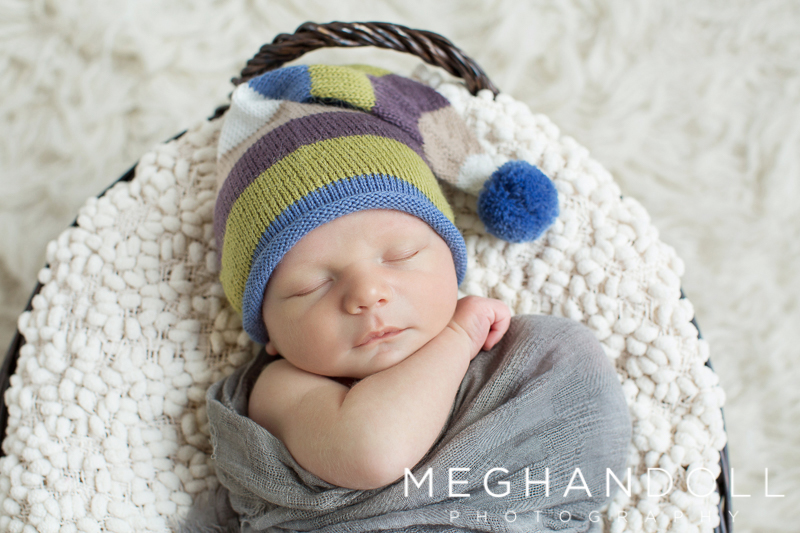 little-newborn-boy-sleeps-in-striped-hat