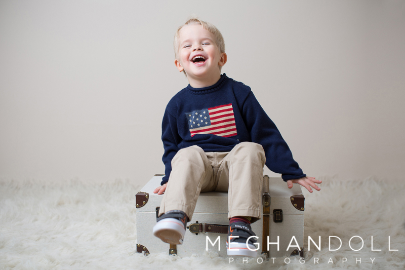 three-year-old-boy-in-flag-sweater-laughs-on-suitcase