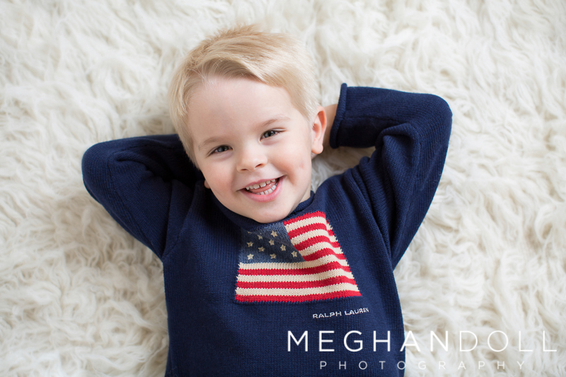 three-year-old-boy-in-flag-sweater-lounges-on-carpet