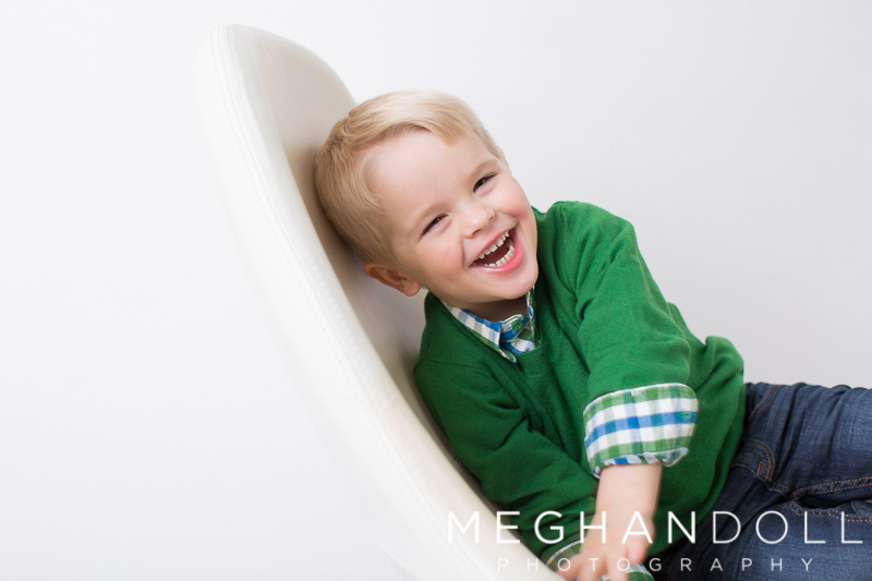 three-year-old-boy-in-green-sweater-laughs-in-big-chair