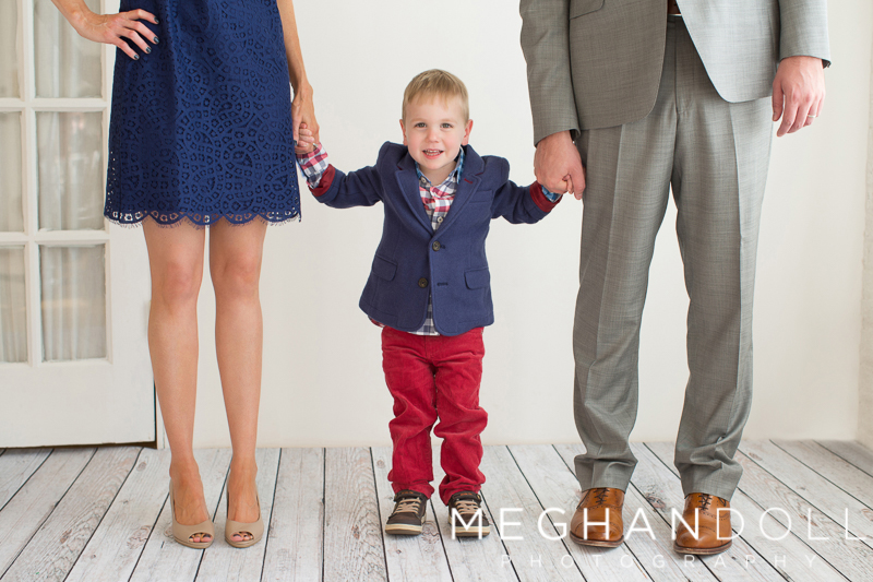 little-guy-in-patriotic-suit-holds-parents-hands