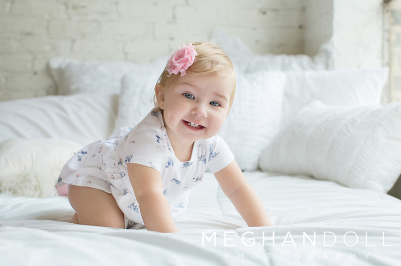 one-year-old-girl-smiles-on-bed