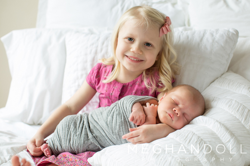 big-sister-in-pink-holds-new-baby-brother