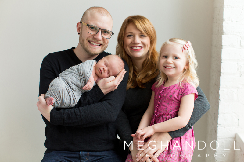 family-of-four-smiles-with-new-baby-boy