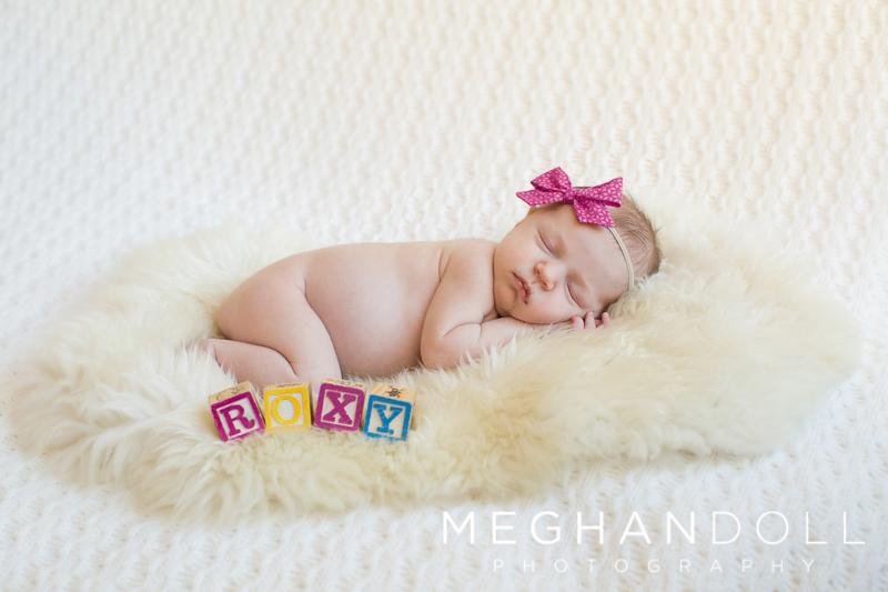 sleeping-newborn-girl-on-fur-with-blocks