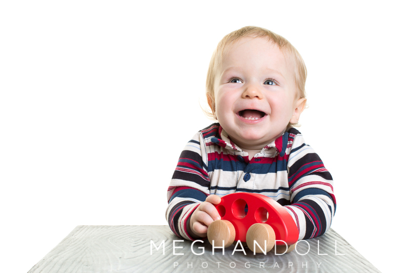 one-year-old-boy-in-stripes-plays-with-red-car