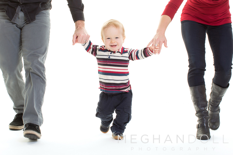 one-year-old-boy-in-stripes-walks-with-mom-and-dad
